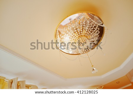 Golden and mirror chandelier with point light on orange ceiling - stock photo