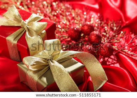 Golden and red gift boxes on a red satin background