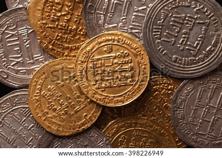 Golden and silver ancient arabic coins closeup, selective focus, top view - stock photo