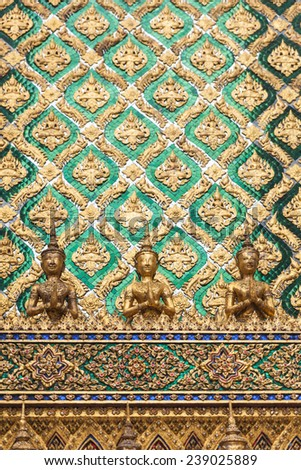 Golden angel statue and decorated wall with thai art - stock photo