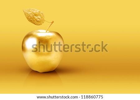 Golden apple on yellow background. - stock photo