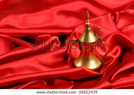 Golden arabic coffee / tea pot in red satin background - stock photo