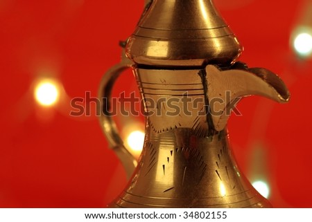 golden arabic tea pot with red blurred lights in the background - stock photo