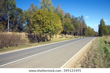 Golden autumn. Empty suburban road with new road markings on cloudless sunny autumn day