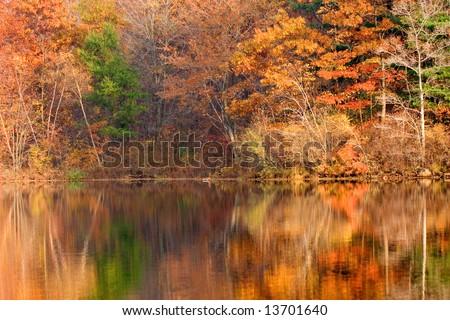Golden autumn foliage around New Jersey lake in Appalachian mountains - stock photo