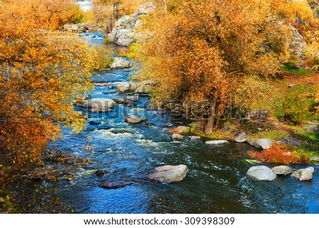 Golden autumn on a mountain river with rough flow - stock photo