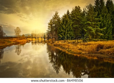 golden autumn sunset above river - stock photo