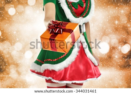 golden background with green woman elf and golden gift and ribbon of red color  - stock photo