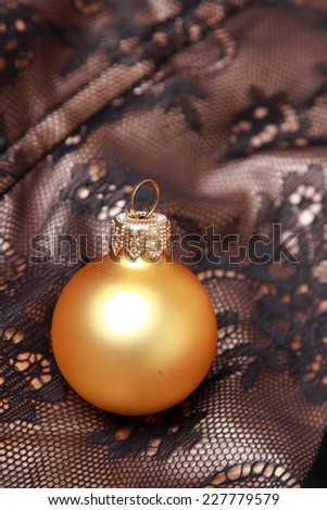 golden ball decoration on Christmas over Black and golden fabric with ornament texture pattern on Holiday theme - stock photo