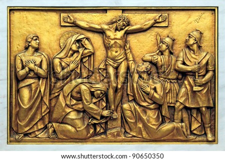 Golden bas-relief of the old Basilica of Fatima representing one of the fourteen mysteries of the rosary, similar to the stations of the cross. This bas-relief depicts Jesus Christ on the Cross. - stock photo