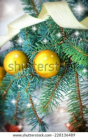 Golden bauble on Christmas tree - stock photo
