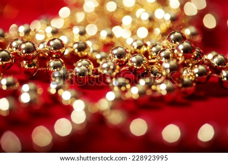 golden beads on red with blurred lights bokeh holiday background  - stock photo