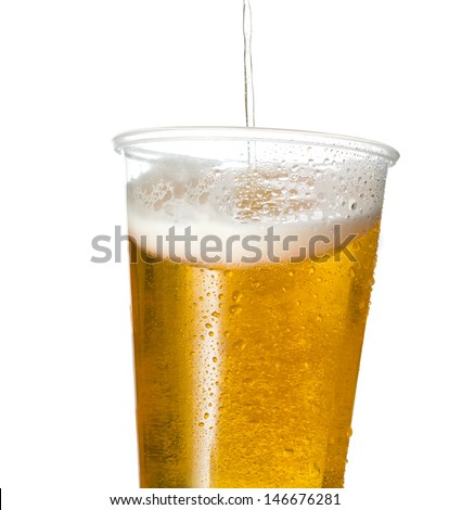 Golden beer, ale or lager in a tilting plastic disposable cup or glass with beer being poured and spilling over edge of pint glass - stock photo