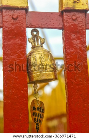 Golden bell on a painted red and gold fence