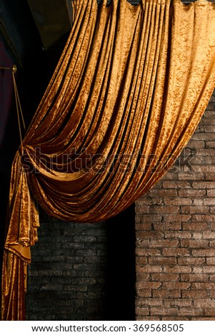 Golden big curtain on brick wall background - stock photo