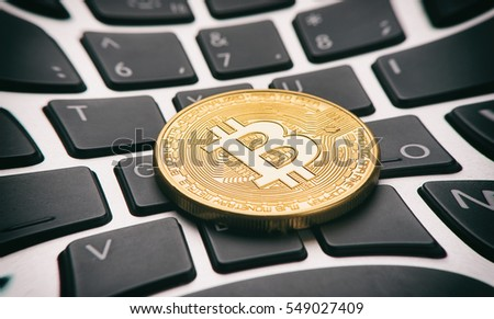 Golden bitcoin coin on a computer keyboard