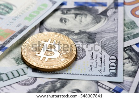 Golden Bitcoin coin on a us dollars close up