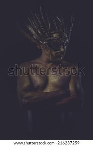 golden bodypaint, man with gold helmet, ancient warrior deity - stock photo