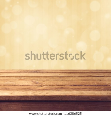 Golden bokeh background with wooden table - stock photo