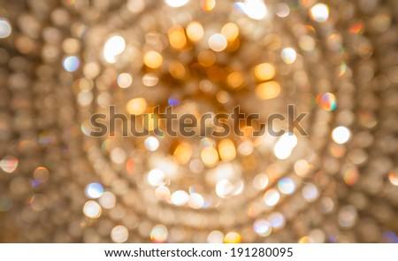 Golden bokeh from crystal chandelier - stock photo