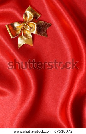 Golden bow on a red silk