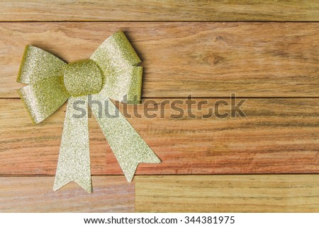 Golden bow ribbon on wood background - stock photo