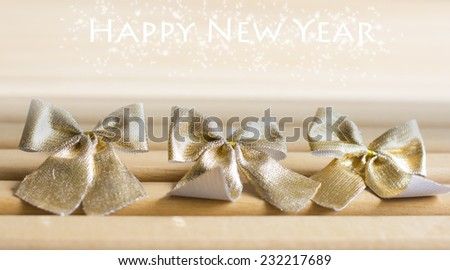 Golden bows tied with text effect on wooden background