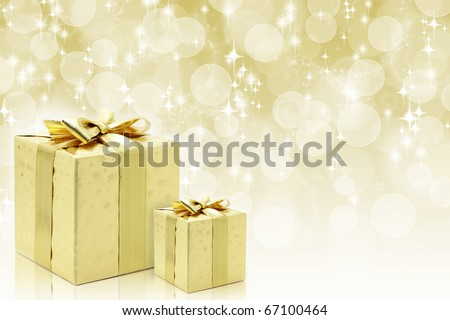 Golden boxes with bow against bokeh background - stock photo
