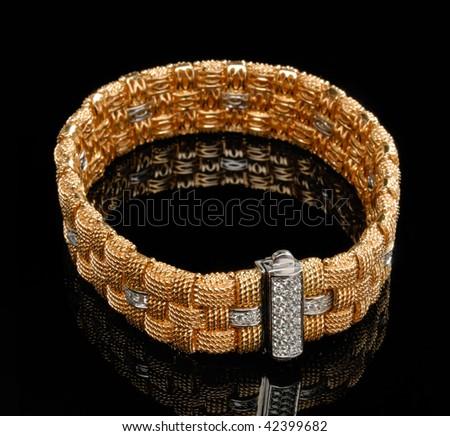 Golden bracelet with diamonds over black background - stock photo