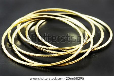 Golden bracelets on black background. - stock photo