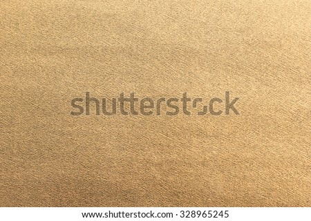 golden bronze color paper texture for background in vintage color tone styles:creased gold paper texture backdrop with grain:detail of paper texture.wallpaper decorate for Christmas festive or etc. - stock photo