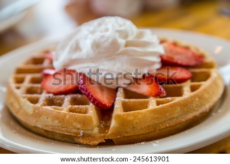 Golden brown waffle topped with sliced strawberries and whipped cream - stock photo