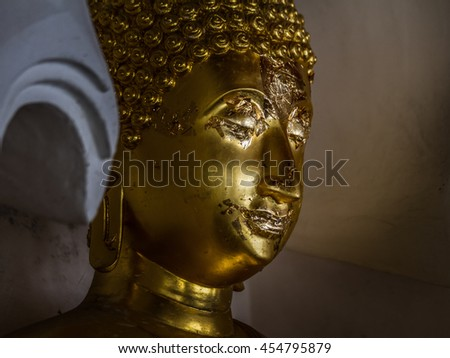 golden buddha face with shadow - stock photo