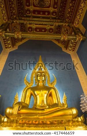 Golden Buddha illuminated from the blue background inside a Thai temple, Bangkok, Thailand. - stock photo