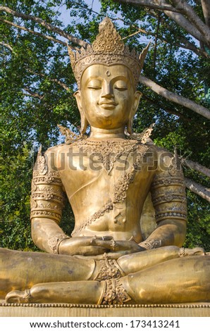 Golden buddha image and green tree background in the ancient buddhist temple ,ChiangMai, Thailand.  - stock photo