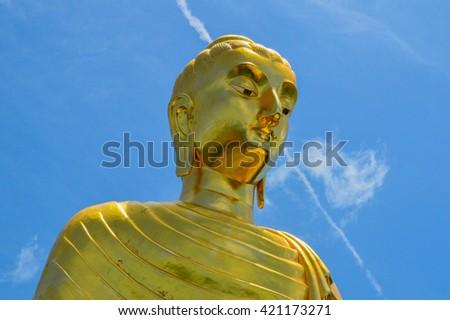 golden buddha image with blue sky - stock photo