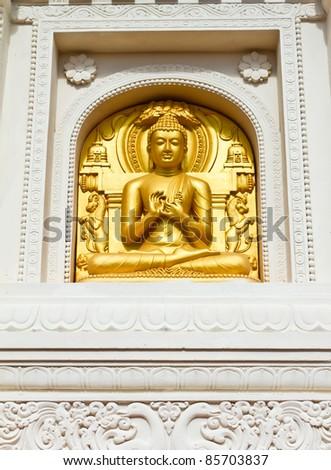 Golden Buddha in White Wall - stock photo