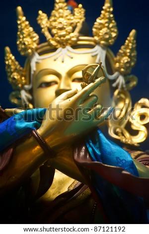 Golden Buddha sculpture in Tibetan Monastery. Focus on hand - stock photo