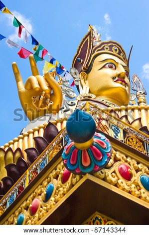 Golden Buddha sculpture in Tibetan monastery over blue sky with praying flags. Focus on hand - stock photo