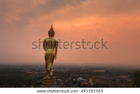 Golden Buddha standing on a mountain Wat Phra That Khao Noi during sunset. in, Nan, Thailand