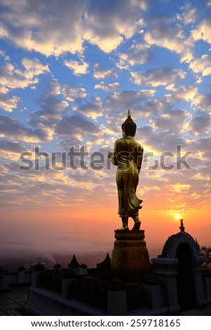 Golden Buddha statue at Wat Phra That Kao Noi with colorful clouds sky in morning, Nan Province, Thailand