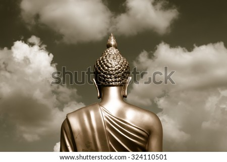 Golden Buddha statue from back focused on head  sepia tone - stock photo