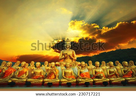 golden buddha statue in buddhism temple thailand against dramatic sun rising with ray beam background - stock photo