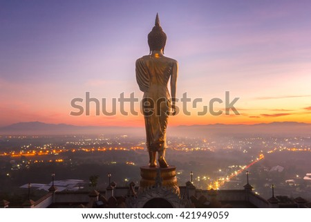 Golden buddha statue in Khao Noi temple at sunrise time, Nan Province, Thailand - stock photo