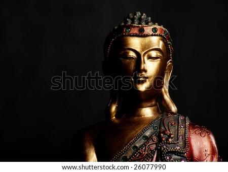Golden Buddha statue on a dark background - stock photo