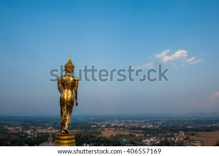 Golden Buddha statue standing on a mountain in Wat Phra That Khao Noi built during the 23rd-25th Buddhist centuries, Nan Province, Thailand, image in blue sky background