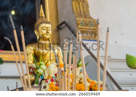 Golden Buddha statue with incense stick - stock photo