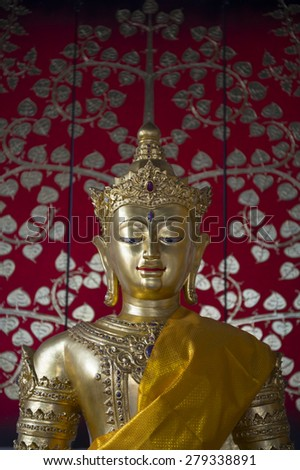 Golden buddha with sash close up against a decorative red background in a Buddhist temple in Bangkok Thailand - stock photo