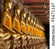 golden buddhas lined up along the wall of buddhist temple - stock photo