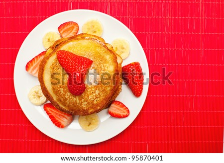 golden buttermilk pancakes with strawberry and banana on red - stock photo